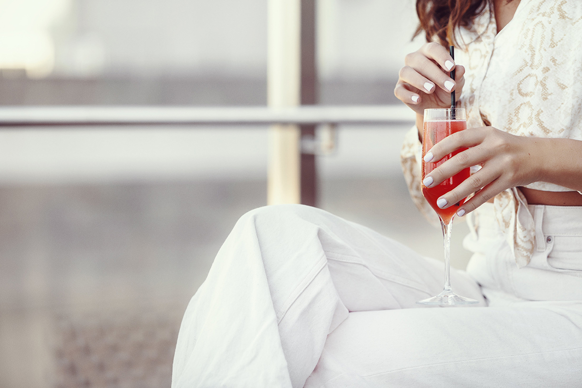 Woman in white holding red cocktail