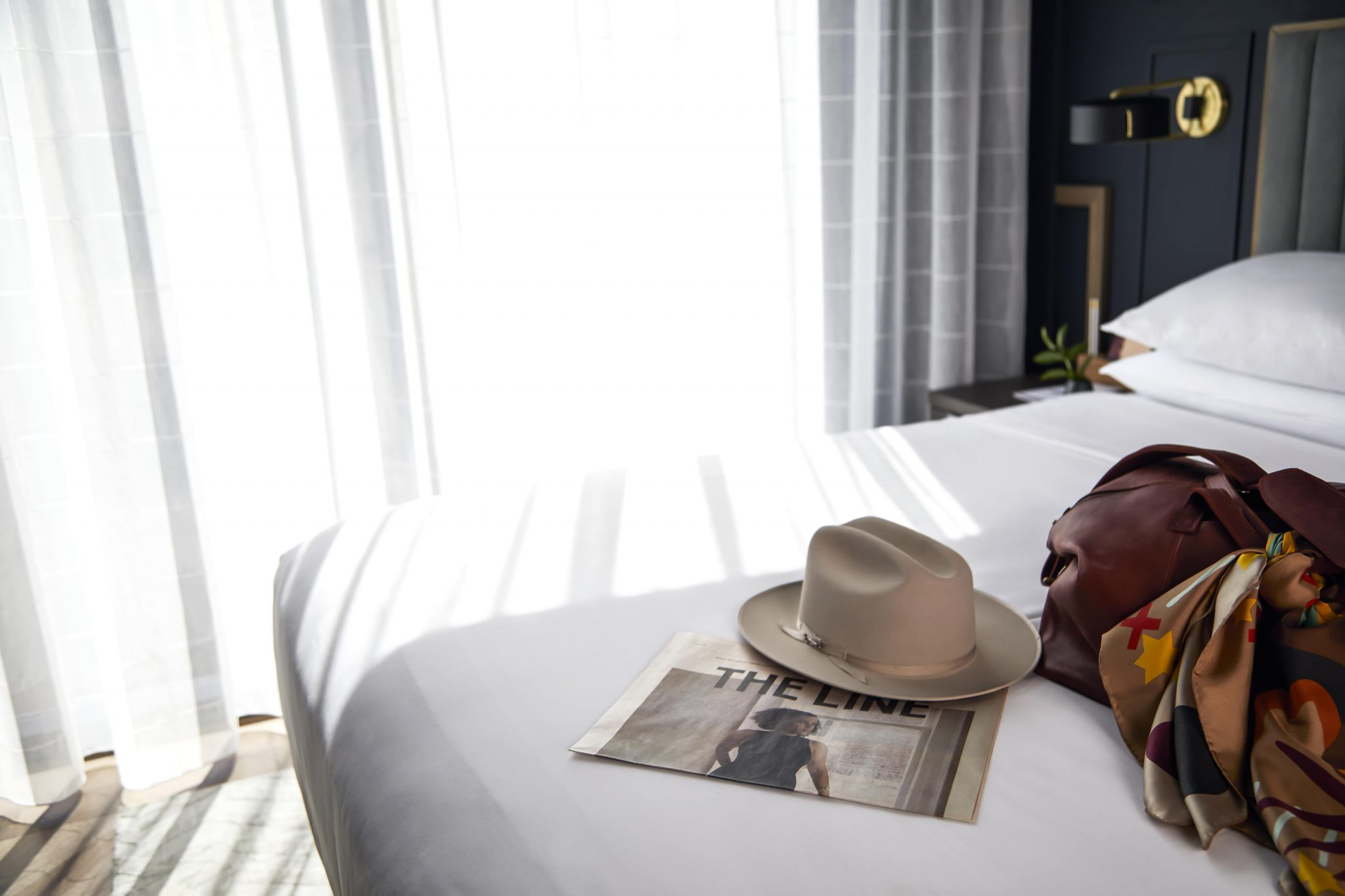 Penthouse Bed with Luggage, Hat & The Line Newspaper on Bed
